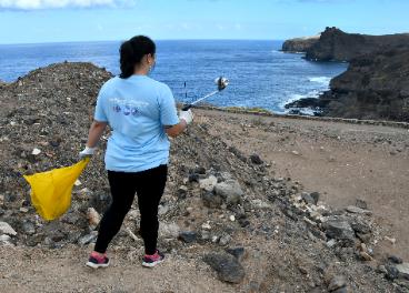 Colaboradora limpiando la playa