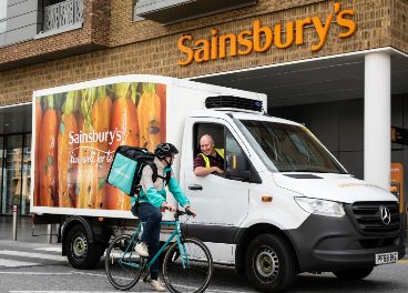 Rider de Deliveroo junto a camión de Sainsbury's