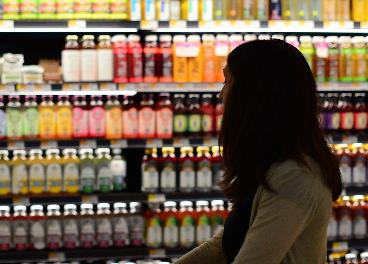 Consumidora frente a un lineal de bebidas