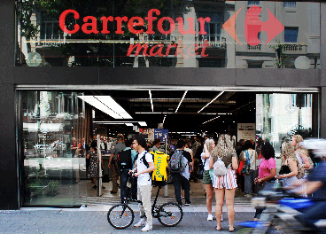 Rider de Glovo ante una tienda de Carrefour